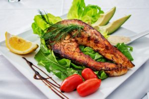 photo of cooked salmon on a plate with salad