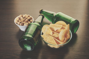 Photo of bottles of beer, potato chips, and nuts on a table.