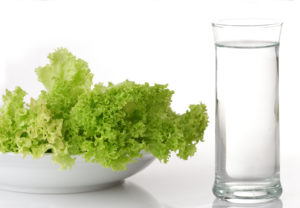 A glass of water and a bowl of lettuce