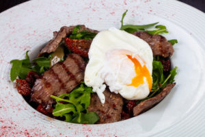 Beef, salad, and a poached egg